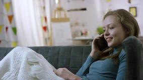 Mulher feliz que tem uma conversa alegre do telefone celular em um sofá video estoque