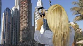 Mulher feliz que toma a foto do selfie no telefone esperto oposto aos arranha-céus do negócio filme