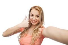 Mulher feliz que toma o selfie e que mostra os polegares acima fotos de stock royalty free