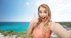 Mulher feliz que toma o selfie e que mostra os polegares acima fotografia de stock