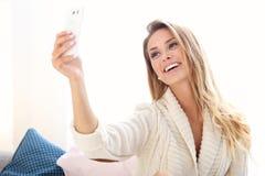 Mulher feliz que toma o selfie na cama fotos de stock royalty free