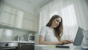 Mulher feliz que trabalha no laptop na cozinha Pessoa fêmea que usa o caderno video estoque