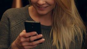 Mulher feliz que usa mensagens texting do telefone celular e sorrindo dentro da loja do café na noite filme