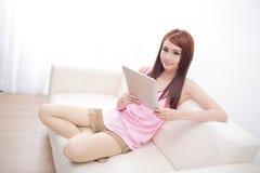Mulher feliz que usa o PC da tabuleta no sofá Fotografia de Stock