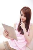 Mulher feliz que usa o PC da tabuleta no sofá Foto de Stock Royalty Free