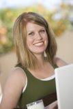 Mulher feliz que usa o portátil Foto de Stock Royalty Free