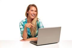 Mulher feliz que usa o portátil assentado na mesa Imagens de Stock Royalty Free