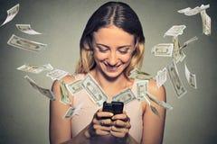 Mulher feliz que usa o smartphone com as notas de dólar que voam longe da tela Fotografia de Stock