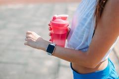 Mulher feliz que usa o smartwatch para resultados das verificações no app da aptidão Braço vestindo do punho do perseguidor do es fotografia de stock royalty free