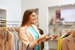 Mulher feliz que usa o telefone app na loja de roupa fotografia de stock