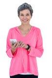 Mulher feliz que usa o telefone celular quando música de escuta Imagem de Stock
