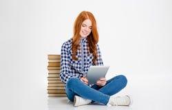 Mulher feliz que usa a tabuleta e sentando-se com os livros atrás dela Imagem de Stock Royalty Free