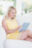 Mulher feliz que usa a tabuleta no sofá Imagem de Stock Royalty Free