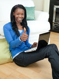Mulher feliz que usa um portátil que senta-se no assoalho Imagens de Stock Royalty Free