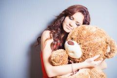 A mulher feliz recebeu um urso de peluche na celebração Imagens de Stock