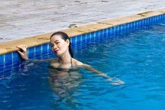 A mulher feliz relaxa na piscina imagem de stock royalty free