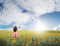 A mulher feliz salta em campos do girassol e no céu azul Imagem de Stock