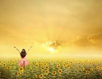A mulher feliz salta em campos e em por do sol do girassol Fotos de Stock Royalty Free