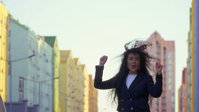 A mulher feliz salta na rua em slowmotion video estoque
