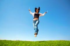A mulher feliz salta no campo Fotografia de Stock Royalty Free