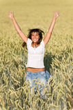 A mulher feliz salta no campo de milho no verão Imagens de Stock