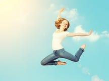 A mulher feliz salta no céu Fotos de Stock Royalty Free