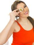 Mulher feliz saudável nova que guarda o sushi do estilo japonês com varas da costeleta fotos de stock