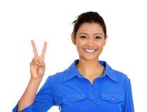 A mulher feliz segura de sorriso que dão a vitória da paz ou dois assinam o gesto Imagem de Stock