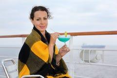 A mulher feliz senta e prende o cocktail Imagens de Stock Royalty Free