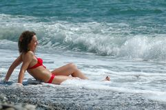 A mulher feliz senta-se na água no seacoast Fotografia de Stock Royalty Free