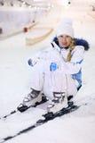 A mulher feliz senta-se no esqui Foto de Stock Royalty Free