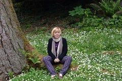 Mulher feliz sob uma árvore entre os wildflowers brancos fotos de stock royalty free