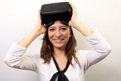 Mulher feliz, sorrindo em uma camisa branca, auriculares vestindo da realidade virtual 3D da falha VR de Oculus, retirando a ou p Imagem de Stock