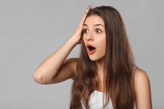 Mulher feliz surpreendida que olha lateralmente no excitamento, isolado no fundo cinzento fotos de stock