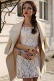 A mulher feminino bonita em lãs elegantes reveste e ata o vestido Fotos de Stock