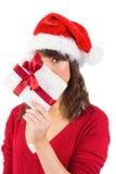 Mulher festiva que olha a câmera que guarda um presente Fotografia de Stock Royalty Free