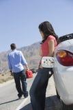 A mulher fica pelo carro enquanto o homem se ajusta fora para a gasolina Fotografia de Stock Royalty Free