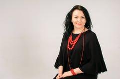 Mulher figurada completa no vestido preto e na colar étnica vermelha que sentam-se na cadeira no estúdio, espaço da cópia no lado Fotografia de Stock