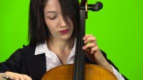 A mulher fixa o violoncelo com seus dedos Tela verde Fim acima video estoque