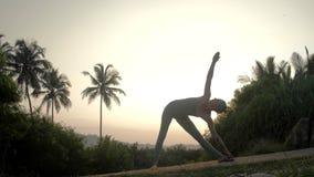 A mulher flexível está no trikonasana no movimento lento da trilha vídeos de arquivo