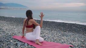 A mulher flexível está relaxando em torcer a pose na costa de mar, apreciando a vista vídeos de arquivo