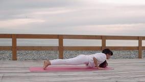 A mulher flexível faz a ioga no ar fresco pelo mar vídeos de arquivo