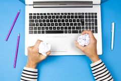 Mulher forçada com o papel de amarrotamento do laptop que tenta vir acima com a solução direita Imagem de Stock