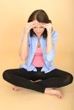 Mulher forçada infeliz nova que senta-se no assoalho com dor de cabeça Imagens de Stock Royalty Free