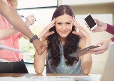 Mulher forçada na mesa cercada pela tabuleta e pelos arquivos do telefone da tecnologia fotos de stock royalty free