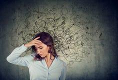 Mulher forçada pensativa com uma confusão em sua cabeça imagens de stock