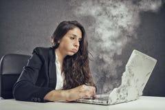 A mulher forçou pelo excesso de trabalho com o derretimento do portátil fotos de stock