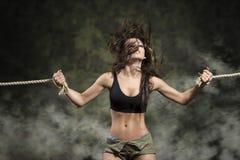 Mulher forte com os pulsos amarrados no vestido 'sexy' Imagens de Stock Royalty Free