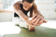 Mulher forte da aptidão que dobra para a frente o esticão de seu pé que senta-se na esteira da ioga imagens de stock royalty free