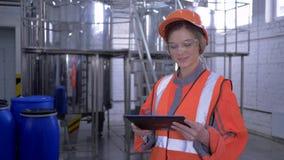 Mulher forte no manufactory, fêmea do operário no capacete e macacão com a tabuleta digital que faz calculado video estoque